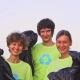 Five Young Volunteers in Green T-shirts with Recycle Image Collect Garbage on an Ocean Beach