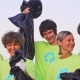 Five Young Volunteers in Green T-shirts with Image Recycle, Collect Garbage on an Oceanic Beach