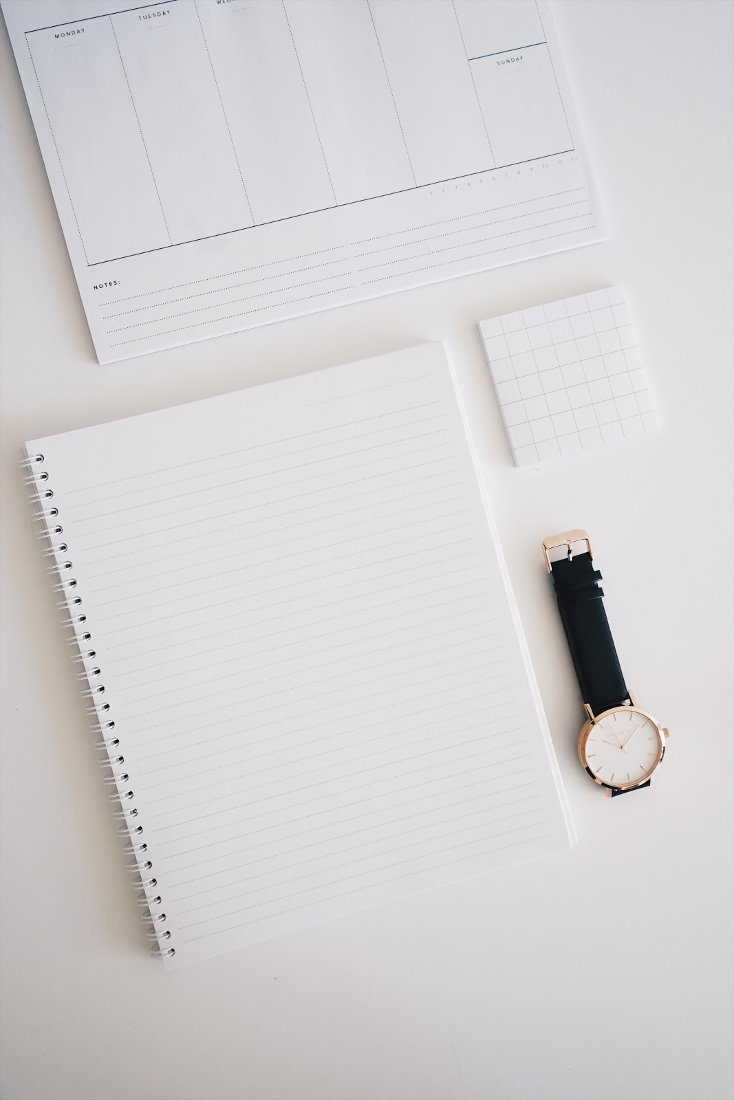 White blank notepad with a coil spine and watch on a clean white desktop.