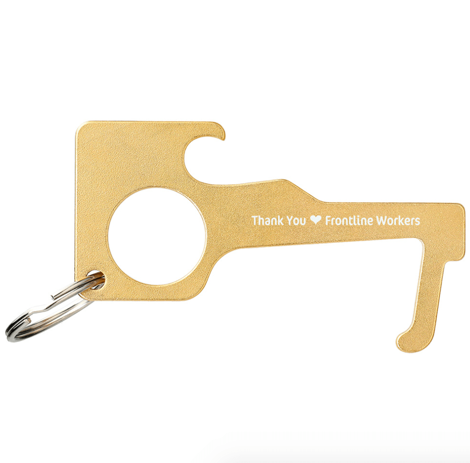 A brass coloured no touch keychain tool that lets you open doors without touching them to be more safe during the pandemic.