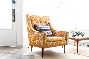 Yellow and comfy chair with a colorful pillow on it