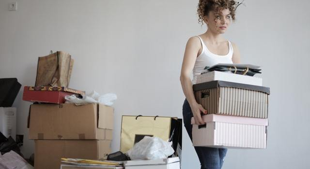 Woman carrying moving boxes.