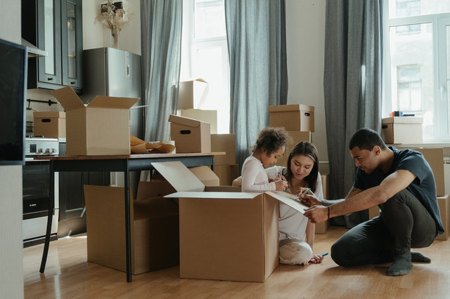 Family packing and talking about expert organizing tips for an easy move.