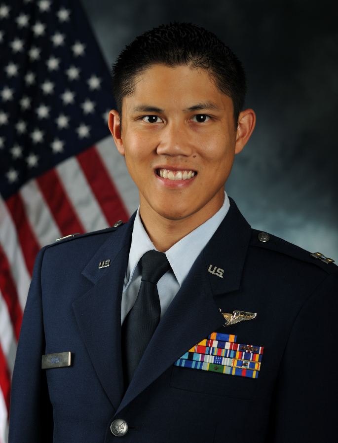 USAF Veteran Matthew R. Quan photographed in his uniform with the U.S. flag draped in the background.