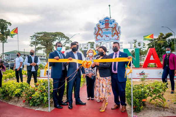 """Guyana's First Lady, Arya Ali, cuts the ceremonial ribbon to launch the """"Welcome to Guyana"""" sign at the CJIA."""