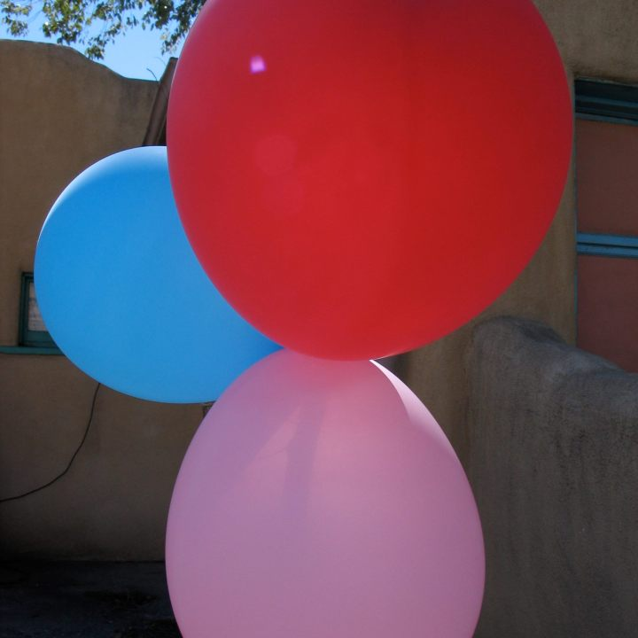 three balloons in blue, red and pink