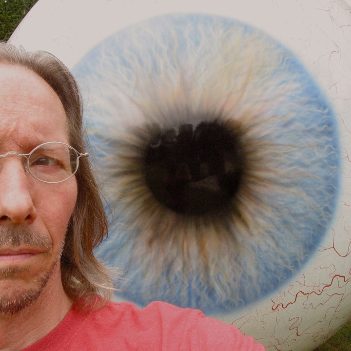 Giant eyeball outdoor sculpture with worried looking photographer