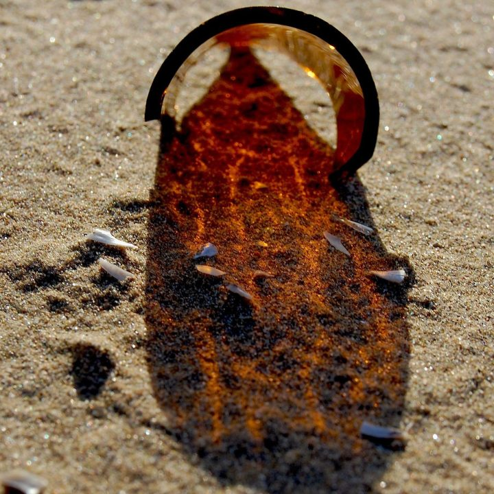 Sun filtering through the brown glass of a broken bottle onto sand