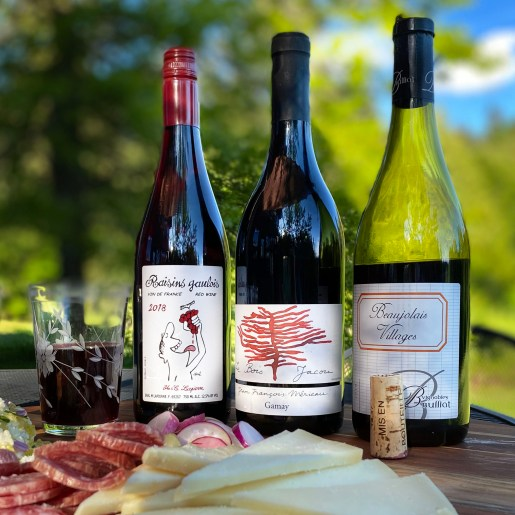 three bottles of wine arranged with meat and cheese