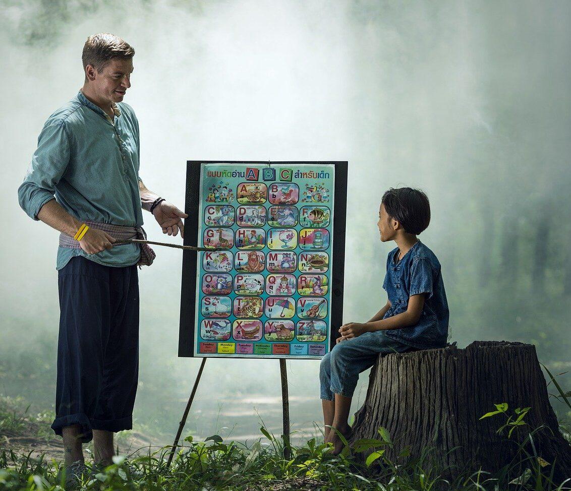 Profesor enseñando a un alumno en medio de la naturaleza