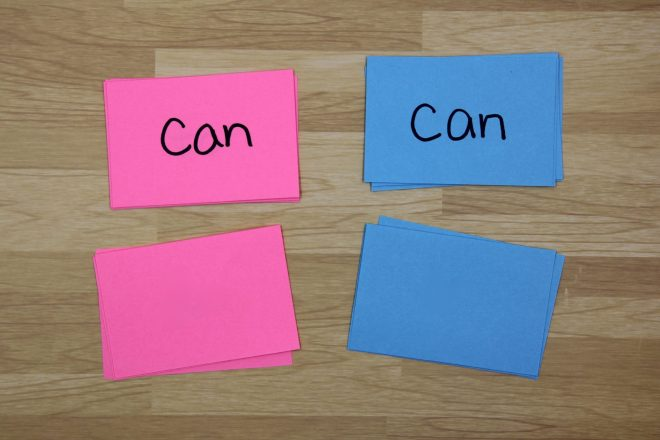 """Photo with two piles of cards on the table (one pink, one blue) and the top card on each pile says """"can."""""""