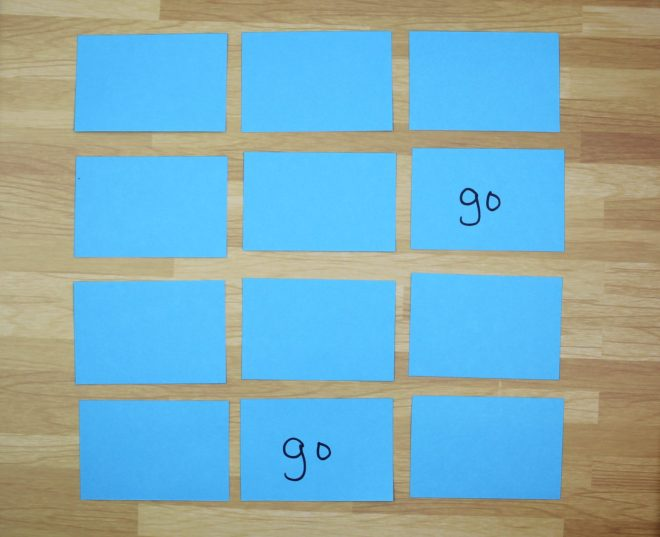 "The memory game is laid out in a  3X4 grid of blue cards with the blank side up. Two cards have been flipped over to show the word ""go."""