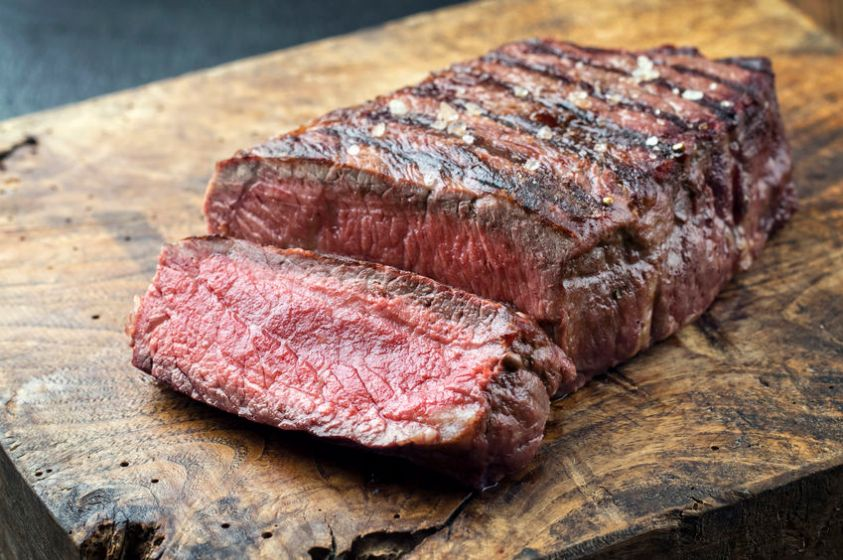 beautifully cut steak on a wooden board
