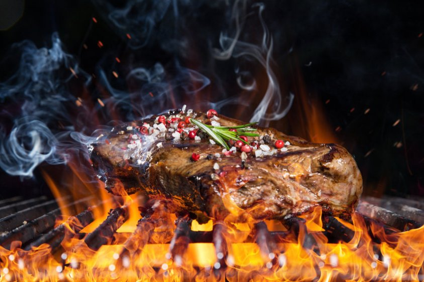Tasty beef steak on cast iron grate with fire flames