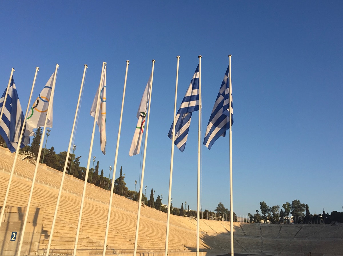 Olympic and Greek flags hang in the foreground of the Panathenaic Stadium in Athens, Greece