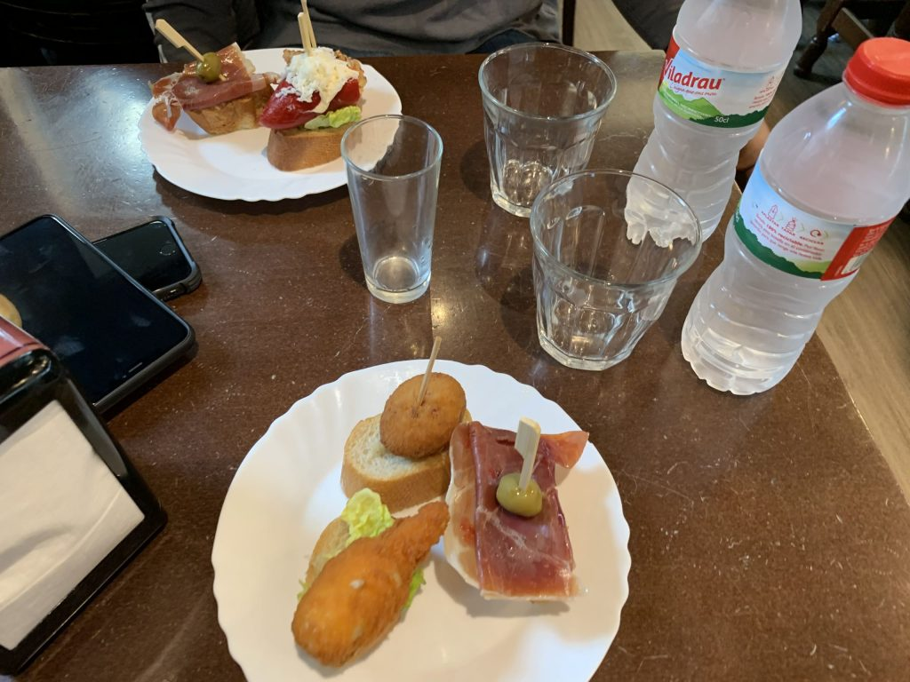 Plate of tapas with water bottles on table