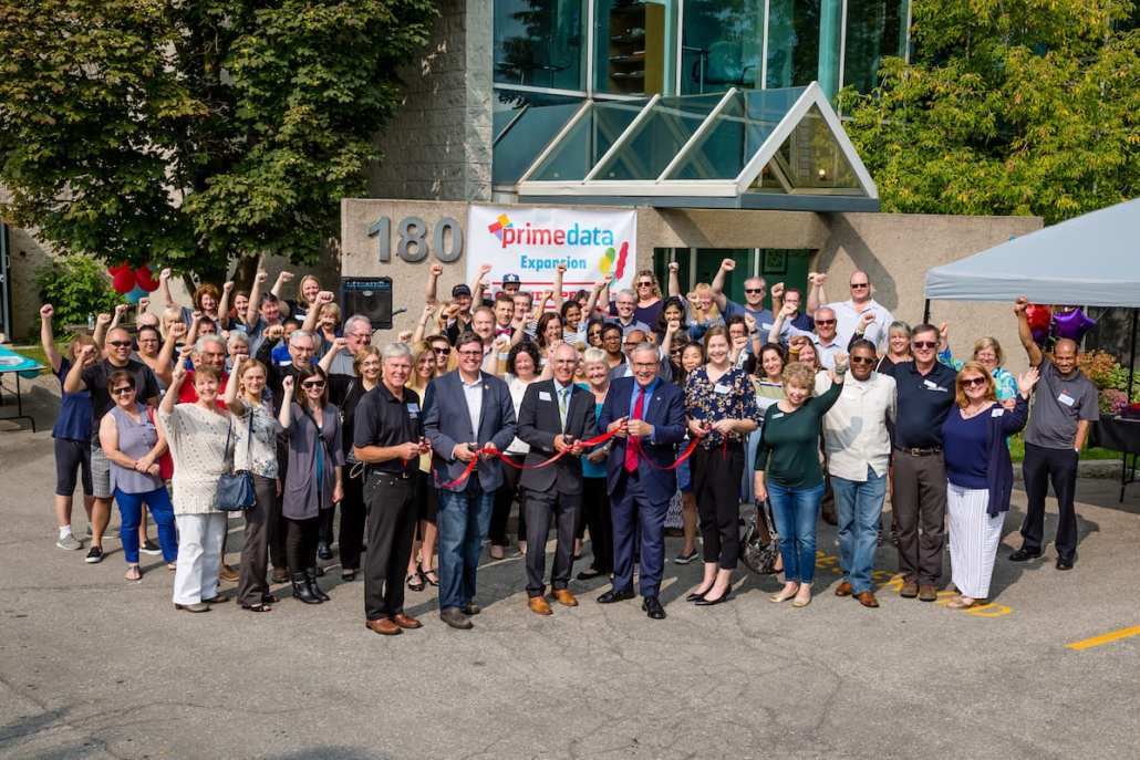 Crowd cheers for ribbon cutting at Prime Data's expanded location