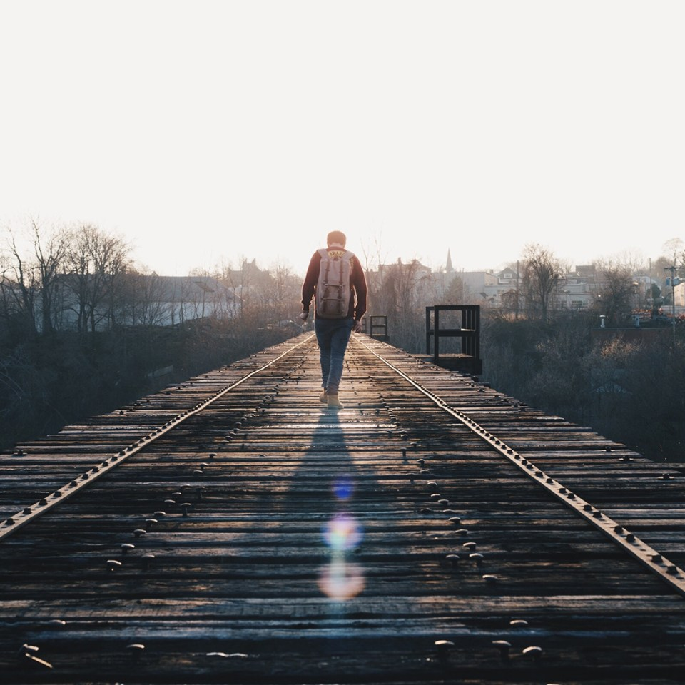 Man Walking on a Wooden Bridge