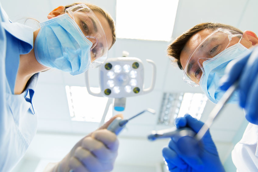 close up of dentist and assistant at dental clinic - Prime Practice North America