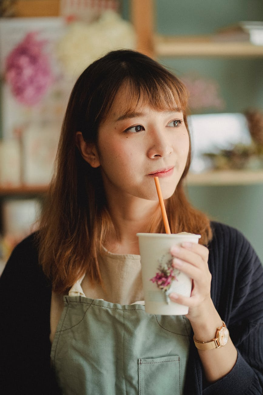 dreamy female with hot drink in paper cup