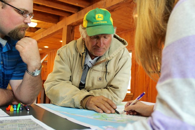 Farmer John Cromwell, 60, discusses drainage issues with members of the city staff at the Creeds Ruritan Barn. He was among dozens of farmers and landowners who traded notes and concerns from April 27-29. [John-Henry Doucette/The Princess Anne Independent News]