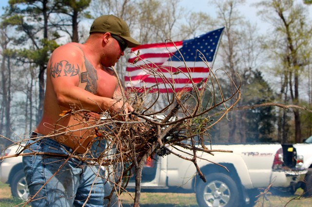Joshua Xenakis, a captain with the city fire department, clears vines on the farm. An army of volunteers have helped support Bukowski's vision for LZ-Grace. [John-Henry Doucette/The Princess Anne Independent News]