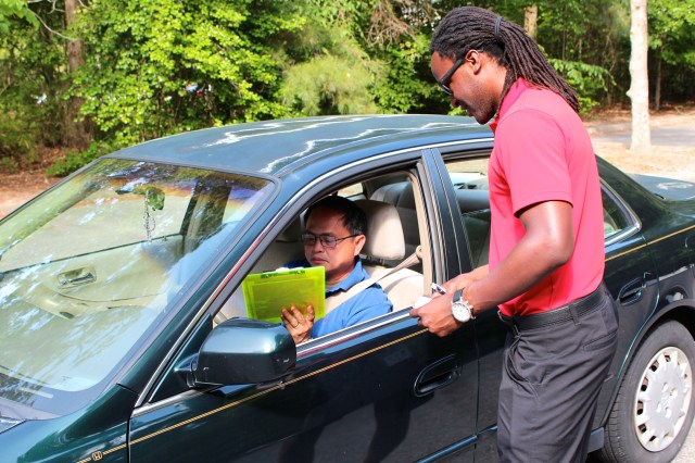 Kelvin Sealy, a revenue agent, helps Das Hurts of Holland Pines during a drive through tax assessment challenge. [John-Henry Doucette/The Princess Anne Independent News]