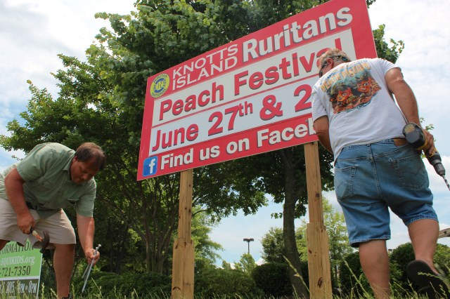 Lee Waterfield, 40, and Buzzy Williams, 67, put up a sign advertising the Knotts Island Peach Festival. [John-Henry Doucette/The Princess Anne Independent News]
