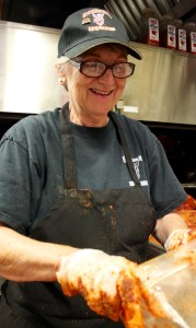 Sue Bell puts the rub one before the pork goes in the smoker. [John-Henry Doucette/The Princess Anne Independent News]