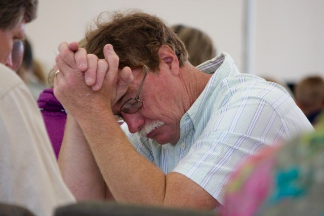"Glenn Taylor of Back Bay, a lifelong member of the church, is deep in prayer during the service. ""I see the vision of it now,"" he said later of the building's potential. [John-Henry Doucette/The Princess Anne Independent News]"