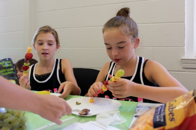Charlotte Scalzi, 10, and Madi Brown, 11, assemble their own snacks of fruit and cheese while being served some Nutella. Both girls are from Lago Mar. [John-Henry Doucette/The Princess Anne Independent News]