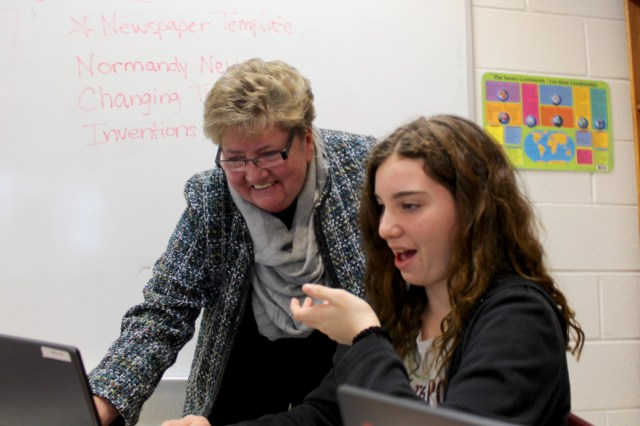 Cotton, in her first year as principal, has placed an emphasis on technology in the classroom. Below, Cotton smiles while Cate Gleim, 12, shows some of her work on a computer. [John-Henry Doucette/The Princess Anne Independent News]