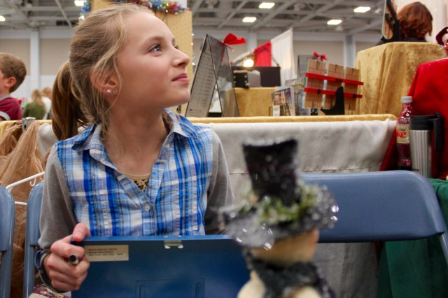 Eleven-year-old Lindsey Starke of Suffolk works with her grandmother's crafting stand during the 34th Annual Virginia Beach Christmas Market at the Virginia Beach Convention Center, held Nov. 27-29. [John-Henry Doucette/The Princess Anne Independent News]