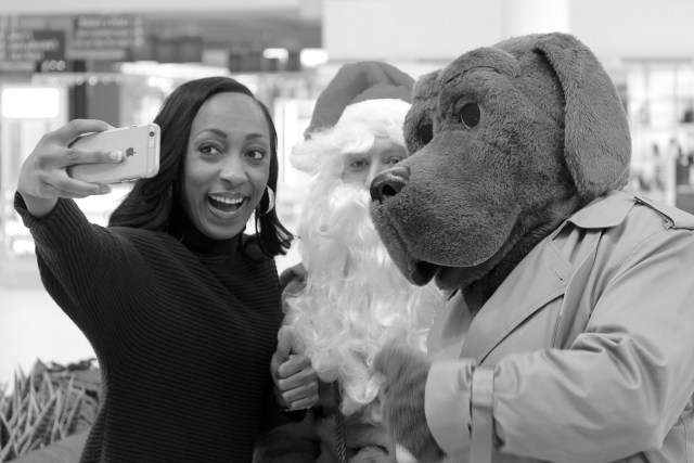 Reporter Stefania Okolie of WTKR-TV takes a selfie with Santa and McGruff. [Th Princess Anne Independent News]