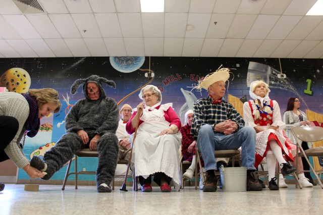 Paul Yocher, dressed as Old Mother Hubbard's dog, gets a costuming assist from office manager Jeanne Keeley at Red Mill Elementary School. With him, in the front row, are Atlantic Shores performers Elsie Stovall, Bob Moje and Jane Moje. [John-Henry Doucette/The Princess Anne Independent News]