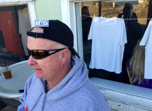Chuck Mullis wears a decorative $2 bill in his ball cap during the gathering to celebrate Jones. In the window are some of Jones' tees, which were on clothes lines on the walls of the restaurant. [John-Henry Doucette/The Princess Anne Independent News]