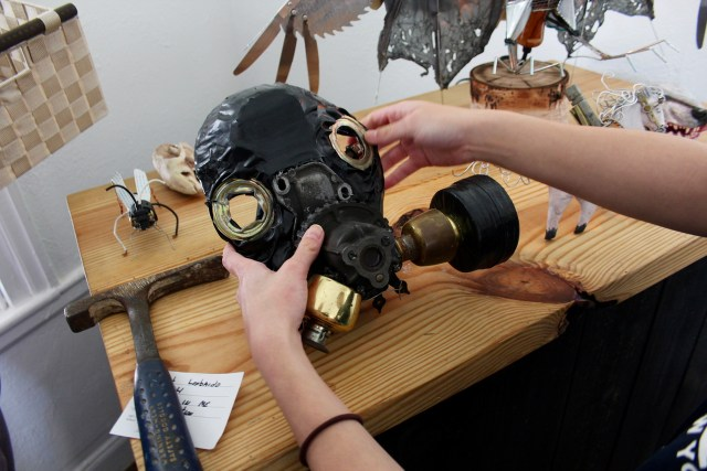 "A gasmask sculpted from objects is placed on display by Hackett, whose other work includes a frog mobster entitled ""Frogeddaboutit."" [John-Henry Doucette/The Princess Anne Independent News]"