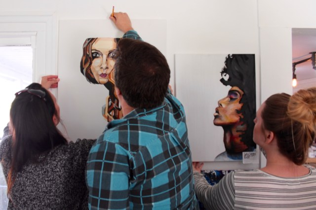 Peters and the Compos work together to hang student art. [John-Henry Doucette/The Princess Anne Independent News]