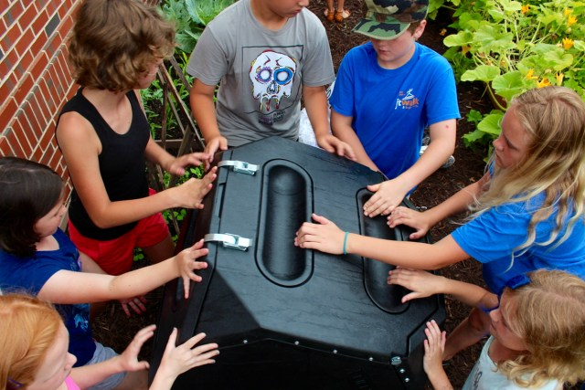 Fourth graders at Creeds Elementary School mix organic material in a compost tumbler while working in a learning garden n Friday, June 17, 2016. [John-Henry Doucette/The Princess Anne Independent News]