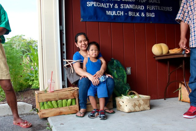 "Maritess Caalim, seen with her son, Alexis, 3, visited the market while visiting family. Her brother-in-law, Mario Caalim of Virginia Beach, often comes to the market, and he said he was buying corn and other produce to cook for his loved ones while they visited. ""I come here almost always,"" he said. ""The price is good."" [John-Henry Doucette/The Princess Anne Independent News]"
