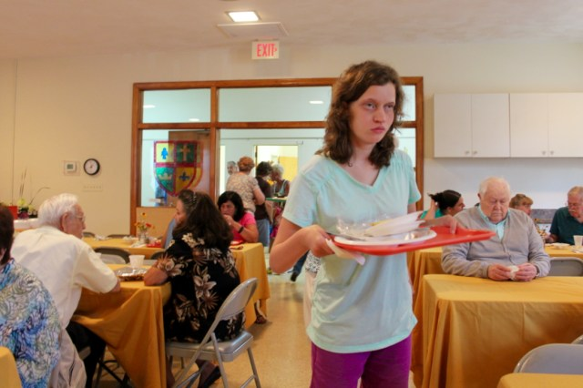 Myra Fisher, 16, of Lago Mar helps clear places during the luncheon. [John-Henry Doucette/The Princess Anne Independent News]
