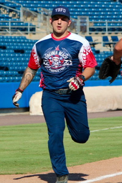 Firefighter Jose Aguerrebere, who is assigned to Station 19 at Stumpy Lake, scores a run during the charity softball game. [John-Henry Doucette/The Princess Anne Independent News]