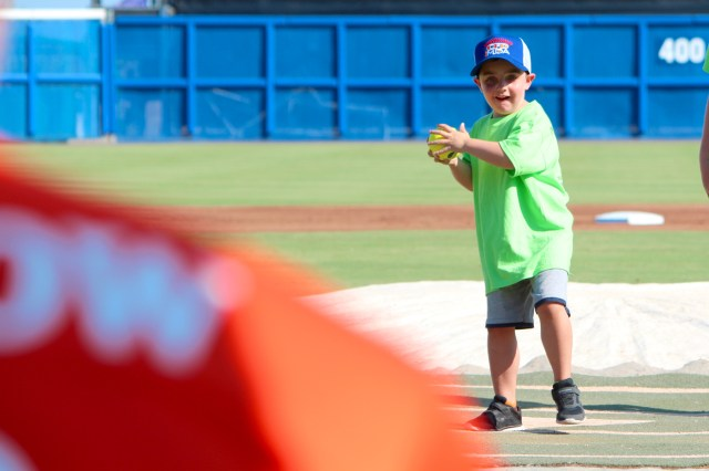 Logan Morean, 4, of Suffolk throws the opening pitch to Chesapeake Capt. Lawrence Matthews, Morean's uncle, before the charity game begins at Harbor Park. [John-Henry Doucette/The Princess Anne Independent News]