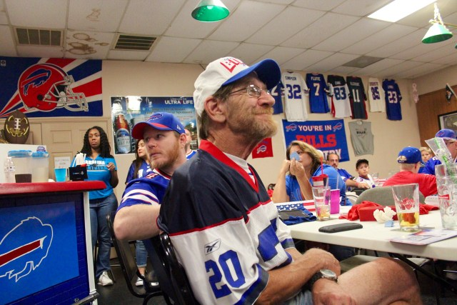Ponch Cabaday, president of the Bills Backers of Virginia Beach, sits after watching the end of the Bills loss on Sunday, Sept. 11, at Mike's Break Room, where the chapter gathers in a room decorated with Bills colors and memorabilia on game day. He watched the game with his son, Sean Cabaday, looking left in the photo, who rejoined the Bills Backers after years away due to work schedules. [John-Henry Doucette/The Princess Anne Independent News]