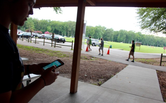 Tess Tucker, 22, of Harpers Square demonstrates Pokemon Go at Red Wing Park. She said the game is social and brings people together. The three young men walking on the path nearby said they were playing, too. [John-Henry Doucette/The Princess Anne Independent News]
