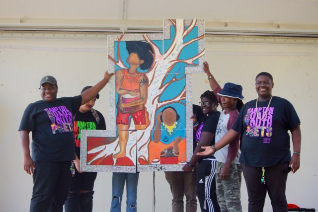 Young people show how the panels of the painting unite. [John-Henry Doucette/The Princess Anne Independent News]