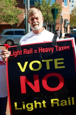 City Treasurer John Atkinson and opponents of extending light rail to Town Center brought signs and flowers to a rally held by their opposition. [John-Henry Doucette/The Princess Anne Independent News]