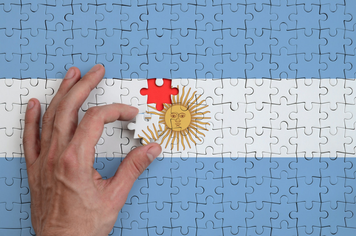 Argentina flag is depicted on a puzzle, which the man's hand completes to fold.