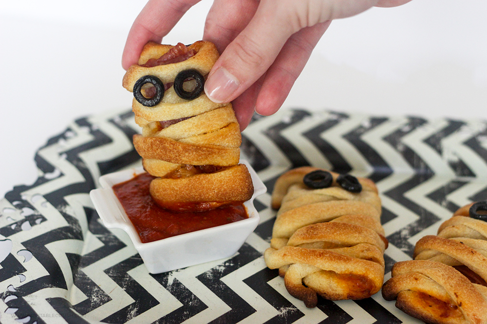Mummy Pizza Bites on black and white tray with hand dipping one is sauce