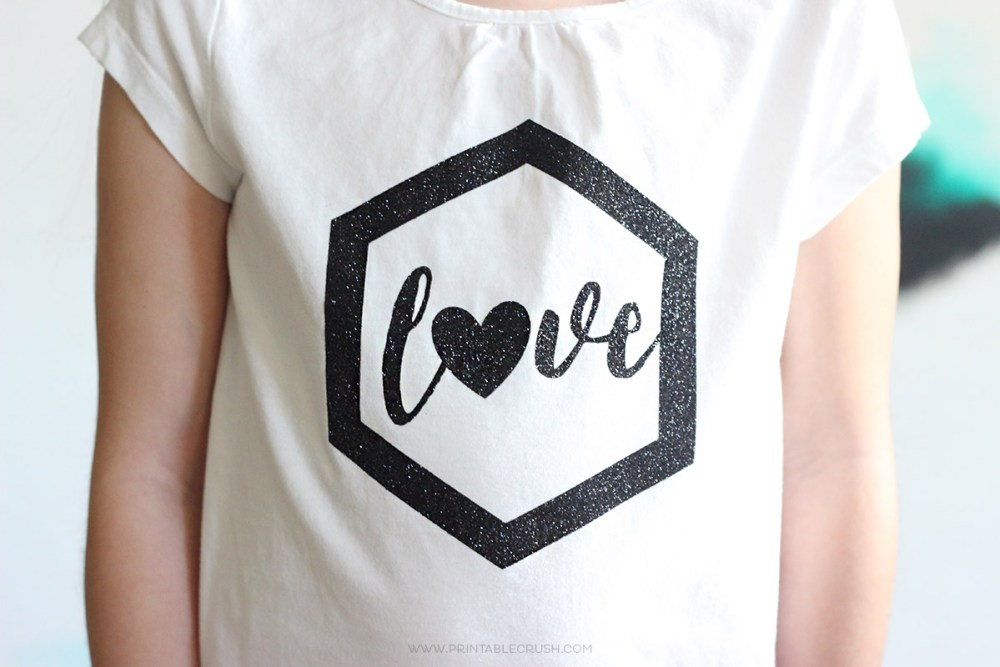 "Front of girl wearing white t-shirt with word ""love"" in black sparkly vinyl"